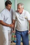 Elder man using a crutches Royalty Free Stock Photo