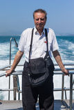 Elder man on vacation. An elderly man travelling on a boat or a ferry royalty free stock photography