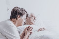 Elder married couple in hospital. Elder married couple sitting in the hospital holding hands and praying Royalty Free Stock Image