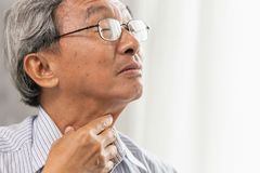 elder old man Sore throat irritation and have a phlegm hand touching neck Stock Photo