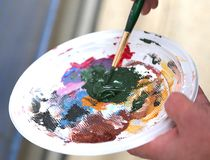 Elder painter mixture the colors in palette Stock Photography