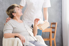 Elder pensioner with assisted living. Nurse giving a box of tissues to elder woman royalty free stock photography