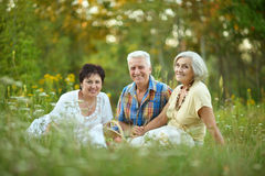 Elder people resting on grass Royalty Free Stock Photography
