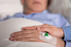 Elder person's hand with venflon. Close-up of an elder patient's hand covered with realative's hand Stock Image