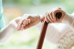 Elder person using walking cane. Elder person using wooden walking cane during rehabilitation in friendly hospital stock image