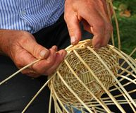 Elder's hands working the cane to create a wicker basket Royalty Free Stock Photography