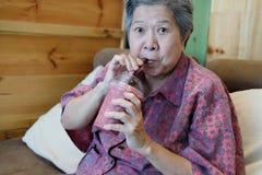 Elder senior lady drinking mixed berries smoothie at home. asian. Cheerful elder senior lady drinking mixed berries smoothie at home. asian elderly woman sitting royalty free stock photo