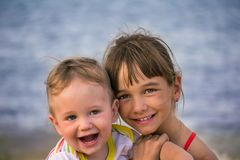 The elder sister with her younger brother hugs happy, sunset Royalty Free Stock Image