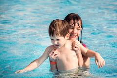 The elder sister holds a younger brother in the children`s pool with blue water. Royalty Free Stock Photography