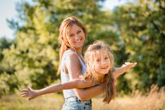 Elder sister playing outdoors with younger on sunny day Royalty Free Stock Photo