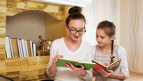 Elder sister reads book for her small sister, girls from christ family spend free time together stock video footage