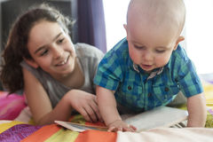 Elder sister reads the book to the brother. The elder sister reads the book to the brother Stock Image