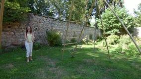 Elder sister swinging smaller on seesaw stock footage