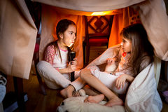 Elder sister telling scary story to younger one at late night Royalty Free Stock Photo