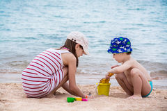 The elder sister and the younger brother are building from the sand on the seashore. Stock Image