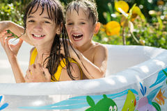 The elder sister and younger brother are indulging in an inflatable pool in the garden, Royalty Free Stock Images