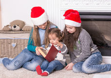 Elder sisters reading a Christmas story his little sister. Stock Photo