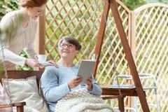 Elder sitting on hanging bench. Elder women reading a book while sitting on hanging bench in garden during meeting with nurse Royalty Free Stock Photos