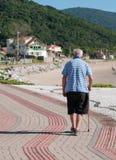 Elder walk on the sidewalk Royalty Free Stock Photo