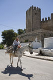 Elder walking in donkey close to the Tower of the  Royalty Free Stock Images