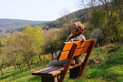 Elder woman. On bench during walk Royalty Free Stock Image
