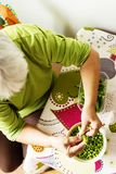 Elder woman cleaning peas from the pods Royalty Free Stock Photography