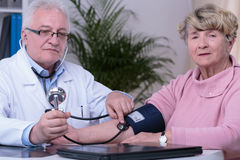 Elder woman controlling blood pressure Stock Image