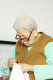 Elder woman doing needlework Royalty Free Stock Image
