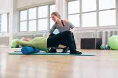 Elder woman doing pilates workout with personal instructor. Female trainer instructing senior women going exercise on a foam roller. Elder women doing pilates Stock Photo