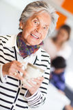 Elder woman drinking coffee Stock Images
