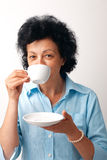 Elder Woman Drinking Tea. Portrait of an elder woman drinking from a cup and holding a saucer Stock Image