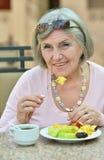 Elder woman eating breakfast Stock Photography