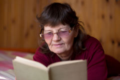 Elder woman engrossed in reading. Cute senior woman in glasses reading a book, lying comfortable on bed at home in cozy rural room with wooden walls, enjoying Stock Images