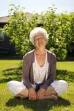 Elder woman enjoying fresh air in garden Stock Images