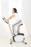 Elder woman on exercise bike Stock Images