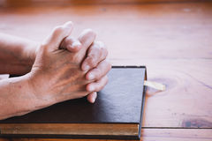 Elder woman hands folded in prayer on a Holy Bible Royalty Free Stock Images
