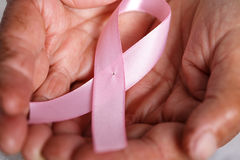 Elder woman hands holding pink ribbon Royalty Free Stock Photos