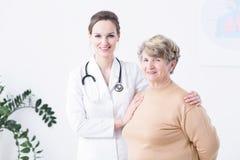 Elder woman with her doctor. Elder women standing with her smiled doctor in bright hospital corridor Stock Photography