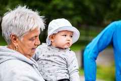 Elder woman holding her grandson in her arms Royalty Free Stock Images