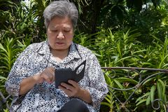 Elder woman holding mobile phone while sitting on bench in garde. Asian elder woman holding mobile phone while sitting on bench in garden. elderly female texting Stock Photos