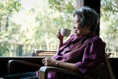 Elder woman holding tea cup on terrace. elderly female relaxing. Asian elder woman holding tea cup on terrace. elderly female relaxing on patio. senior drinking stock image