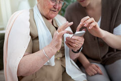 Elder woman learning to use smartphone Stock Photos