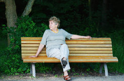 Elder woman on park bench Stock Images