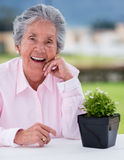 Elder woman with a plant Stock Image