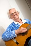 Elder woman playing guitar. Stock Photos