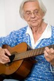 Elder woman playing guitar. Stock Photo