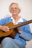 Elder woman playing guitar. Royalty Free Stock Photo