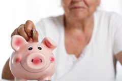 Elder woman putting pin money coins into pink piggybank slot Stock Image