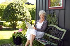 Elder woman reading newspaper in backyard garden. Relaxed elder woman sitting on a bench in backyard garden reading a newspaper looking at camera and smiling Stock Photo