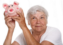 Elder woman shaking funny piggybank. And listening sound of inside detecting amount. Budgeting expenses concept. Making savings and effective investment concept Stock Images